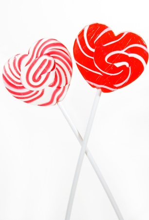 retro style red , pink heart shape lollipop on white background photo