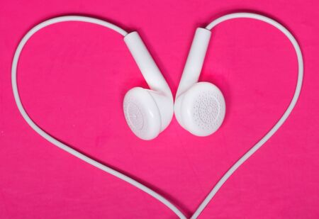 White earphone on pink background look like heart shape photo