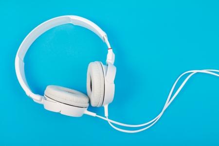 Modern white headphone isolated on blue background  Stok Fotoğraf