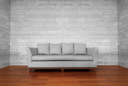 Gray couch chair on brown wooden floor and white wall