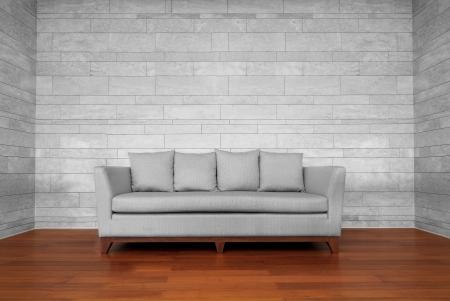 Grijze bank stoel op bruine houten vloer en witte muur
