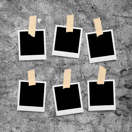 Sticky tape on paper photo frame isolated on grunge cement wall  photo