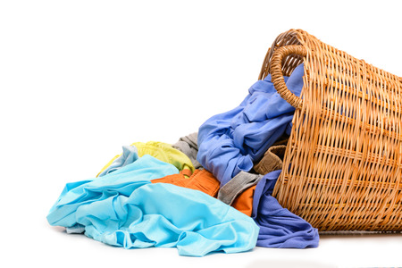 vestidos: Cesta de la ropa completa de mimbre aislada sobre fondo blanco Foto de archivo