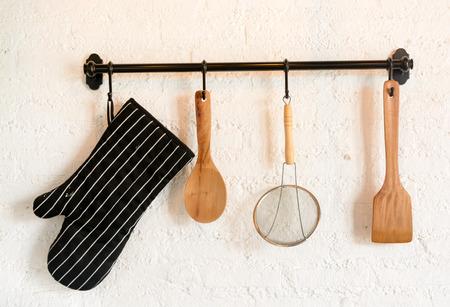 kitchen utensil hang on white stone wall