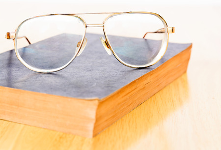 Vintage eyeglasses on dark background with row of old books ...