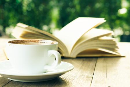 Coffee break and open book on wooden table in garden Standard-Bild