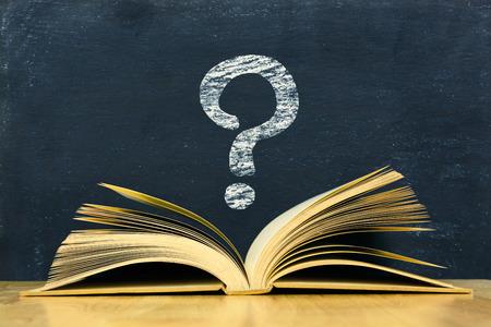 marca libros: Símbolo de interrogación por encima de libro viejo de la vendimia en fondo de la pizarra