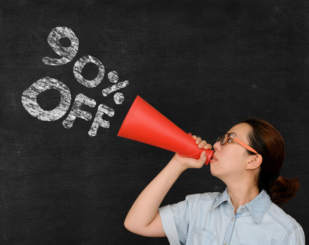 sales person: 90 percent off sale announcement by asian woman on chalkboard background Stock Photo