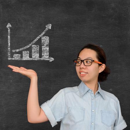 show business: Asian woman show business profilt improvement graph sign on chalkboard Stock Photo