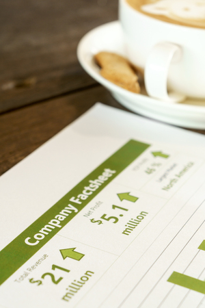 fact: Drinking coffee while reading company financial fact sheet Stock Photo