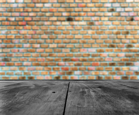 grunge wood: Old rough black wooden table with brown orange brick wall