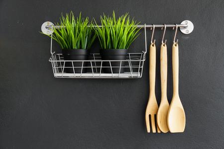 utensils: kitchen utensil hang on black stone wall