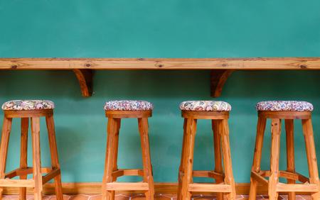 Vintage wooden stool chair on green background restaurant