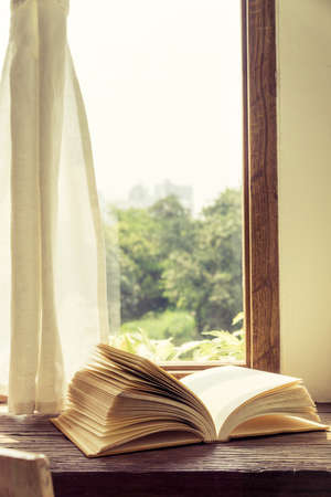 old desk: Old book open on wooden desk and window curtain vintage style Stock Photo
