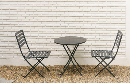Outdoor Steel Chair On White Brick Wall Stock Photo
