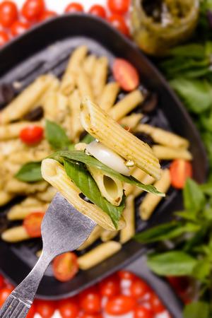 black olive: Penne pesto sauce pasta with grape tometo and black olive Stock Photo