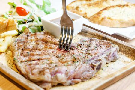 the medium: Medium rare tbone beef steak on wooden plate