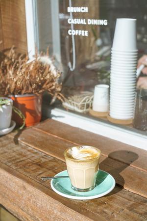 tarde de cafe: Por la tarde taza de café con leche caliente en mostrador de madera al aire libre junto a la ventana de cristal blanco