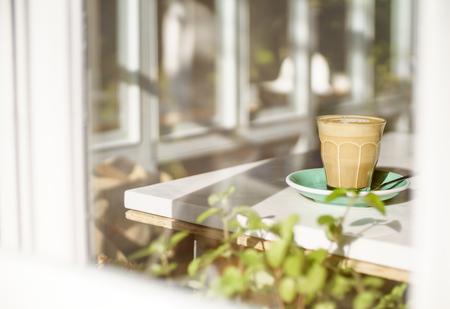 tarde de cafe: Por la tarde taza de café con leche caliente al lado de la ventana blanca de cristal de disparo desde fuera