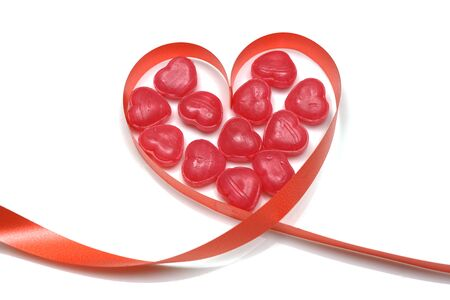 red ribbon and candy toffee heart shape isolated on white background
