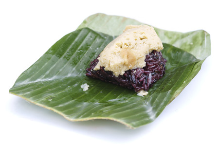 Thai custard sticky black rice dessert on banana leaf isolated on white backgorund