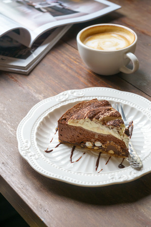 Chocolate cake and hot coffee latte on vintage wooden table