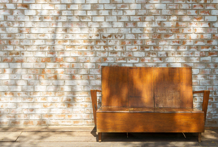 Shadow light on vintage ooden couch with white orange brick wall background texture