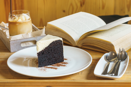 Ice coffee and chocolate cake on wooden table for breakfast leisure
