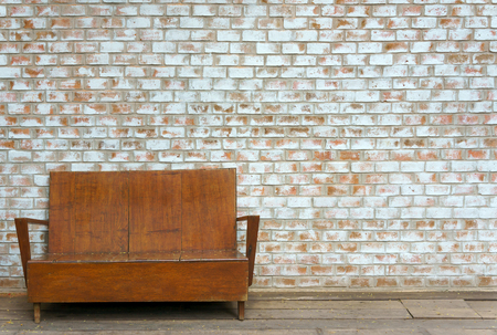 Vintage old outdoor wooden couch on white orange brick wall background texture Imagens