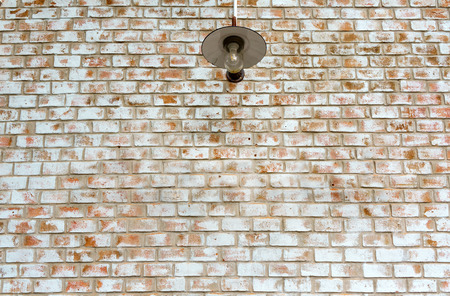 Electricity light lamp bulb on orange white brick wall background texture