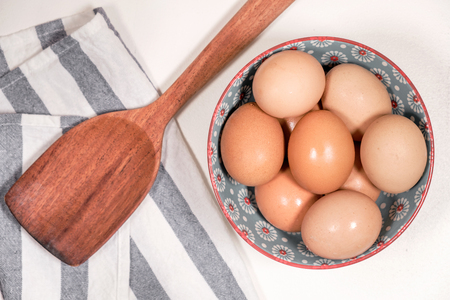 Eggs in bowl and wooden turner utensil