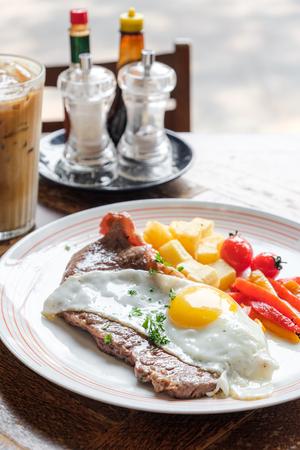 Beef medium sirloin steak with fried egg potato and tomato Imagens