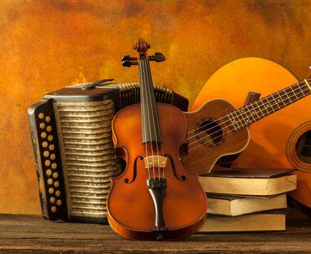 acordeón: Acústica instrumentos musicales de la guitarra ukelele violín y acordeón con el libro de la vendimia ponen en suelo bien pintado y telón de fondo de la pared de la decoración de interiores web sigue el estilo de vida