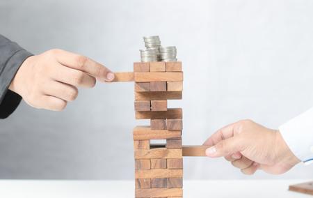 Planning, risico's en strategie in zaken, zakenman die houten blok op een toren gokken plaatsen