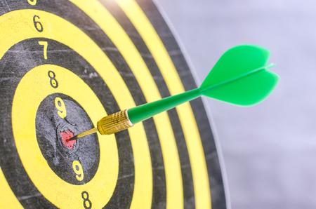 Smart goal setting, dart hit the center of dartboard with light bulb on backgroun