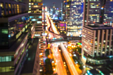 Blurred abstract background aerial view of Bangkok cbd downtown city night lights colorful bokeh in cool vintage cyan turquoise blue tone: Central business district on electric train line over river