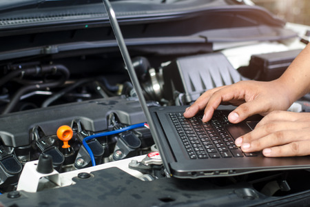 Detail of a mechanic using electrnoic diagnostic equipment to tune a car Archivio Fotografico