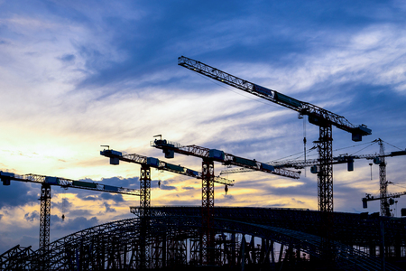 Silhouette Crane in building construction site on Sunset Background Stock Photo