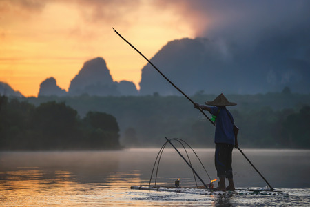 Nong Thale, Krabi, Thailand – July 23,2017. A fisherman with his floating bamboo raft is fishing with a net in Nong Thale, a little swamp in Krabi under the sunrise.