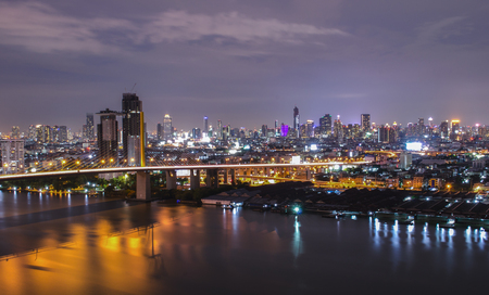 a view over the big asian city of Bangkok , Thailand at nighttime when the tall skyscrapers are illuminated