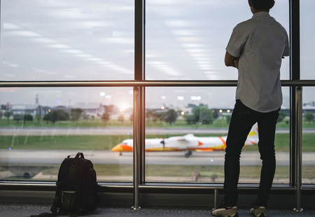 Travel tourist standing with luggage watching sunset at airport window. Unrecognizable man looking at lounge looking at airplanes while waiting at boarding gate before departure. Travel lifestyle.
