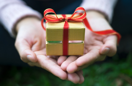 Close up shot of female hands holding a small gift wrapped with red ribbon. Small gift in the hands of a woman outdoor. Shallow depth of field with focus on the little box.
