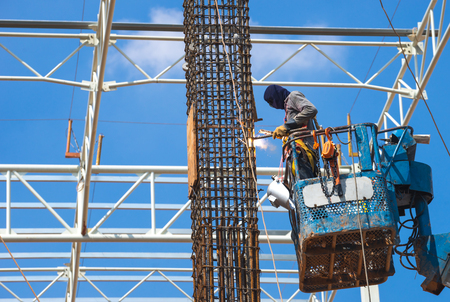 Man Working on the Working at height construction worker at construction site using lifting boom machinery Reklamní fotografie