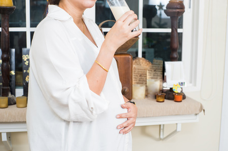 pregnancy, people and healthy eating concept - happy smiling pregnant woman drinking 