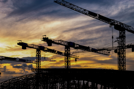 Silhouette crane at construction Site during sunset Stock Photo