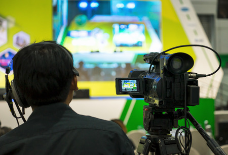 Cameraman working with announcer in broadcast television green screen studio room and professional camera