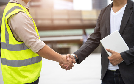 Construction industry, Engineer shaking hands with architect in the town