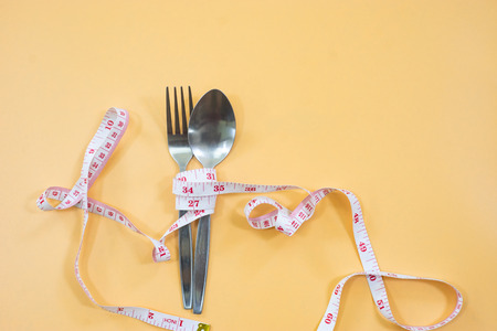 Measuring tape wrapped around fork lying on color surface. Diet concept Reklamní fotografie