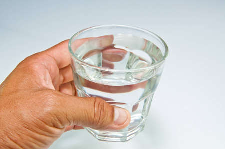 ingest: Hand with a water glass Stock Photo