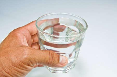 sediento: La mano con un vaso de agua Foto de archivo